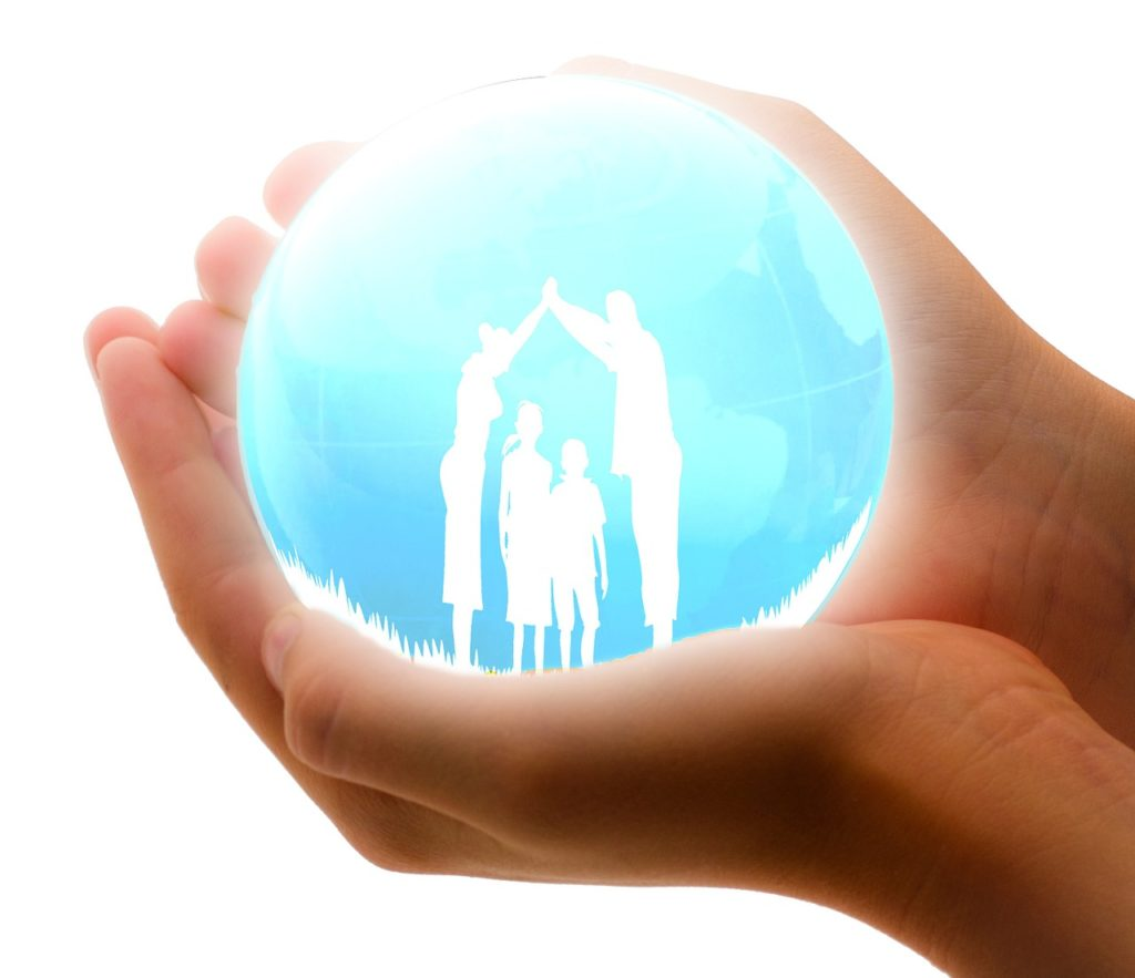 Une main tient une boule de cristal avec une famille dessinée en silhouettes à l'intérieur