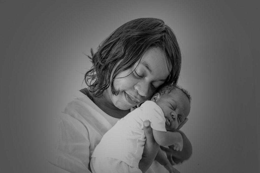 Une jeune femme fait un câlin à un bébé