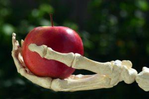Une pommebien rouge tendue par une main squelettique