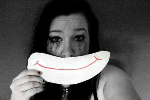 Une femme en détresse porte un masque sourire