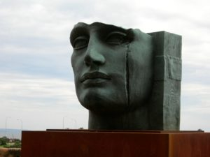 Un visage féminin scculpté. Le front est arraché, une coulée creusée comme un sillon de larmes gravé dans la joue
