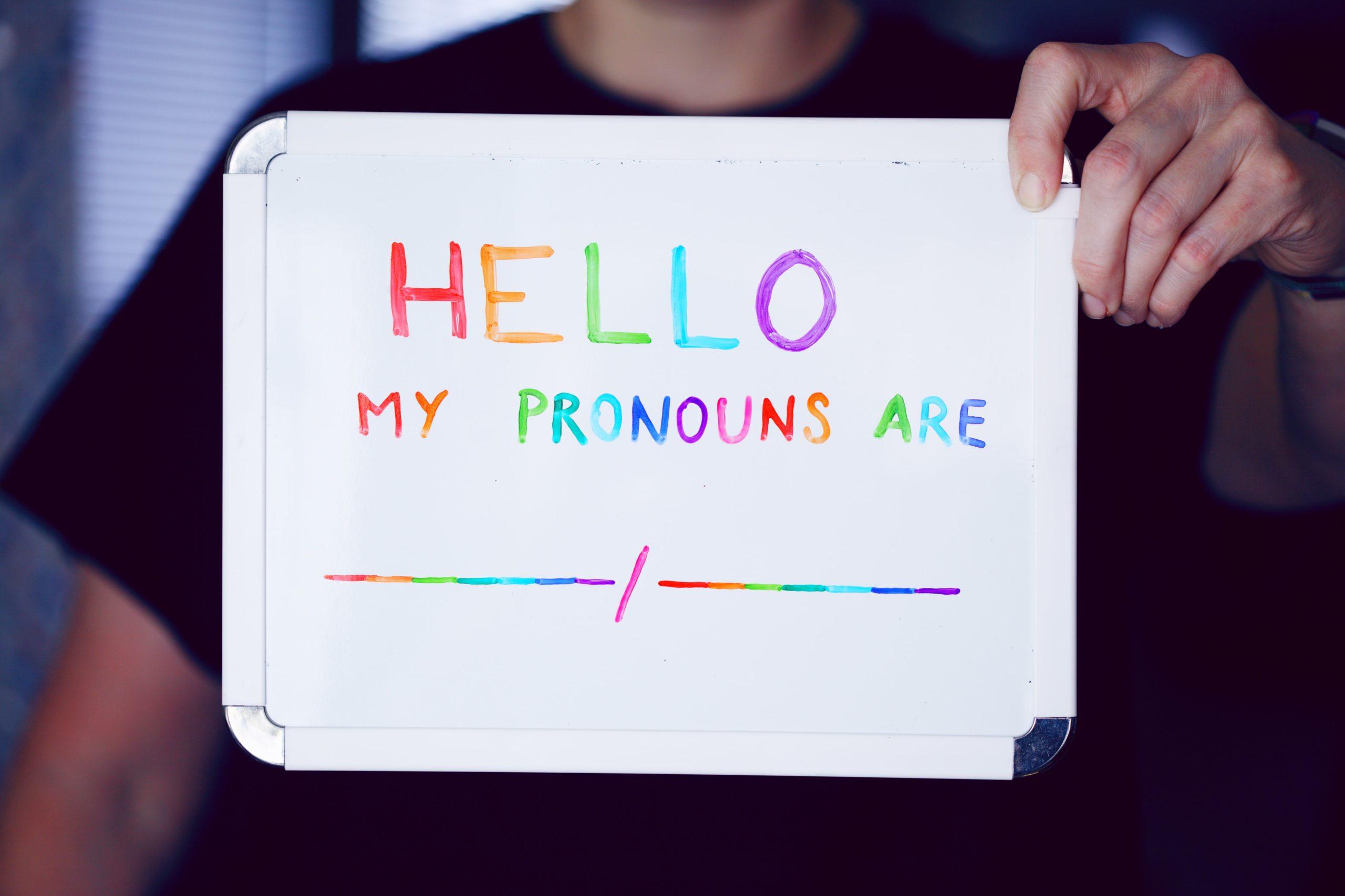 """Une ardoise où des lettres multicolores forment les mots """"Hello, mes pronoms sont..."""""""